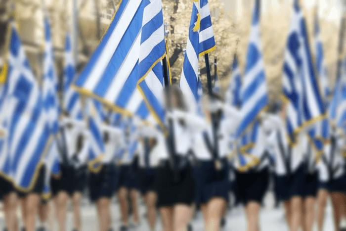 Μαθήτριες κάνουν παρέλαση κρατώντας την ελληνική σημαία