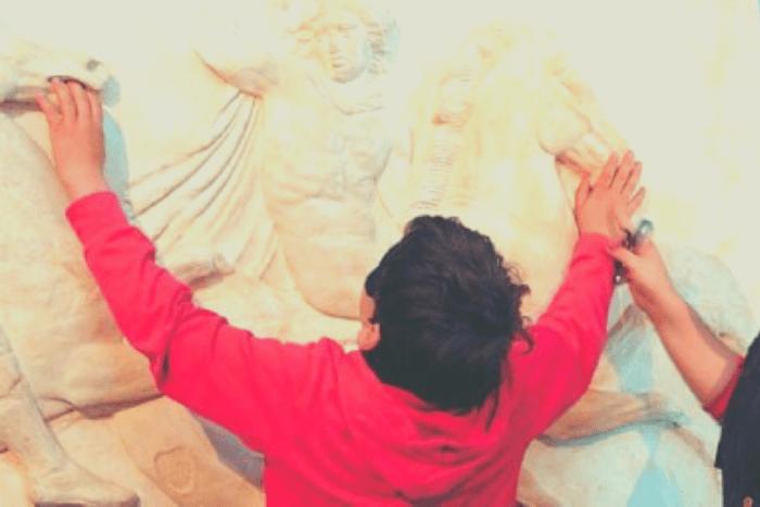 παιδί αγγίζει επιτύμβιες στήλες