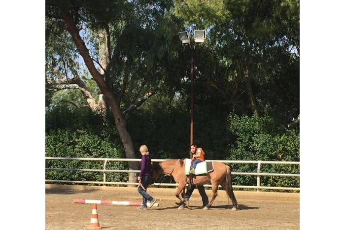 παιδί πάνω σε άλογο κάνει ιππασία