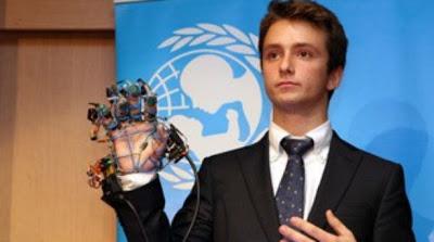 Ο Χάρης Ιωάννου φοράει το μεταλλικό γάντι στην βράβευσή του από τη Unicef