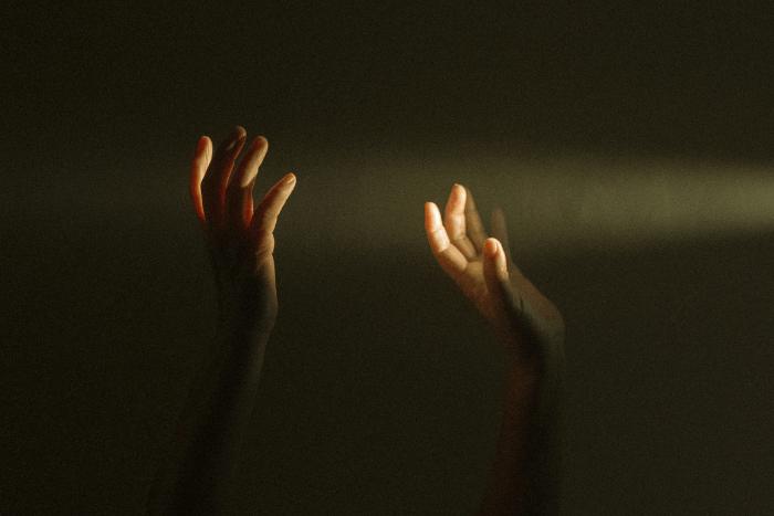 δύο χέρια ψηλά στο σκοτάδι