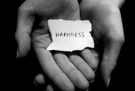 Δύο χέρια που κρατάνε ένα χαρτάκι που γράφει ευτυχία