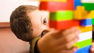 Ένα μικρό παιδί με αυτισμό παίζει με τα τουβλάκια του