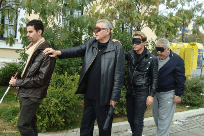 Ο Βαγγέλης Αυγουλάς με λευκό μπαστούνι και από πίσω του με μάσκες και στη σειρά κρατώντας ο ένας τον ώμο του άλλου οι Δημήτρης Κωνσταντάρας, Χάρης Ασημακόπουλος, Πασχάλης Τερζής