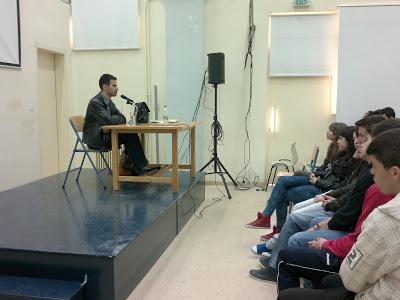 Ο Βαγγέλης Αυγουλάς κάθεται στην έδρα και μιλά στα παιδιά ενώ εκείνα τον ακούν με προσοχή
