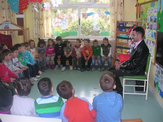 Ο Βαγγέλης Αυγουλάς κάθεται και μιλάει στα παιδιά τα οποία κάθονται κυκλικά γύρω του