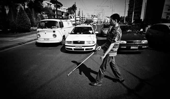 Ο Βαγγέλης Αυγουλάς με το Λευκκό μπαστούνι περνάει λεωφόρο