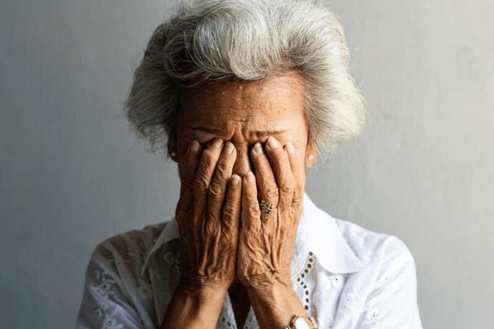 ηλικιωμένη γυναίκα που έχει τα χέρια της στο πρόσωπο της