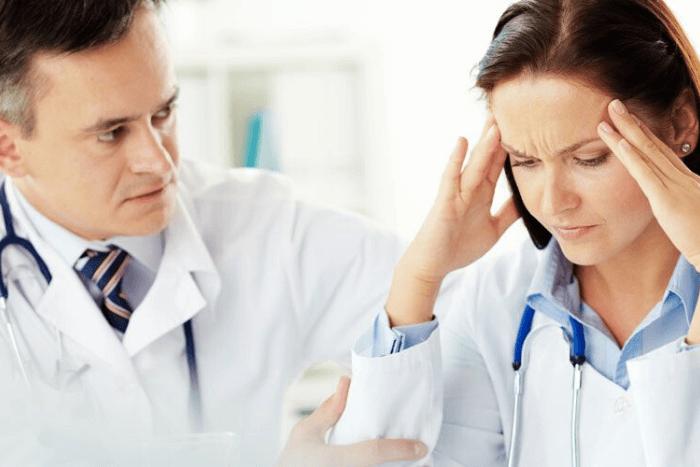 ένας άντρας και μια γυναίκα γιατρός, όπου η γυναίκα κρατάει στεναχωρημένη το κεφάλι της
