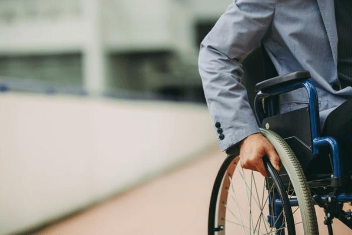 ρόδα αναπηρικού αμαξιδίου που κάθεται άνδρας επάνω