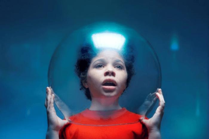 κορίτσι που κρατάει μπροστά στο πρόσωπό της μια γυάλινη μπάλα