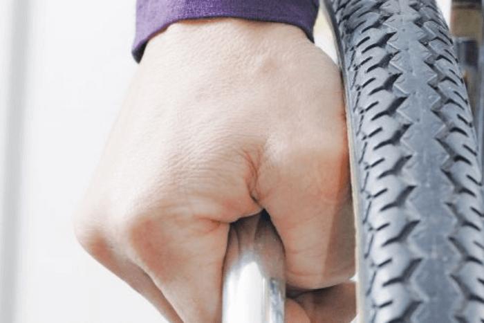 ρόδα αναπηρικού αμαξιδίου και χέρι χειριστή