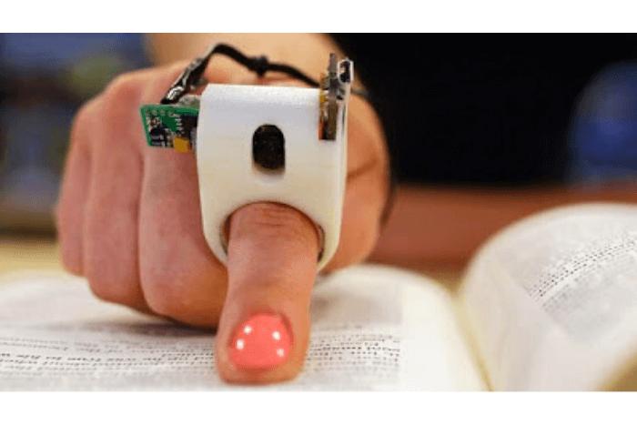 δάχτυλο που φοράει τη συσκευή που διαβάζει φωναχτά και ακουμπάει σε σελίδα βιβλίου