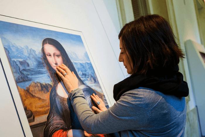 τυφλή γυναίκα αγγίζει πίνακα