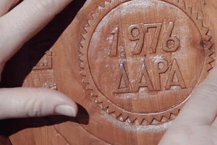 χέρια που αγγίζουν την επιγραφή του Μουσείου