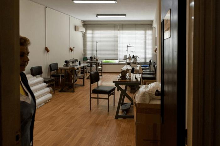 Εργαστήριο ραπτομηχανών γυναίκα στην πόρτα