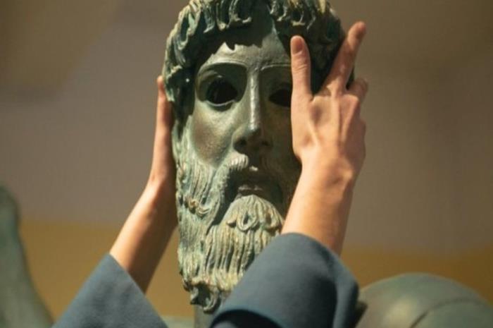 χέρια που αγγίζουν άγαλμα