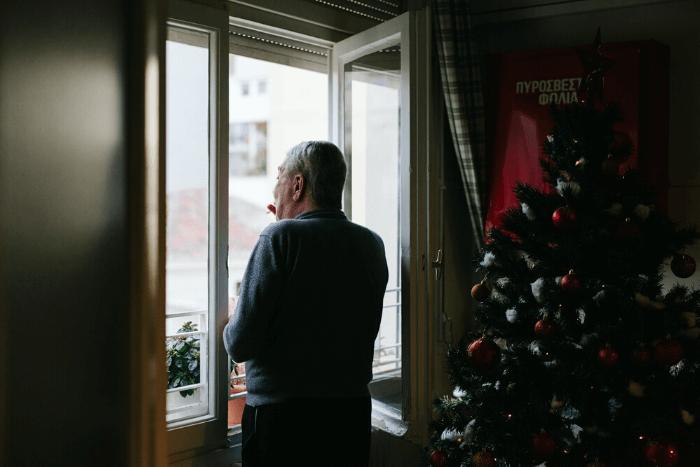 Ηλικιωμένος άντρας μπροστά σε παράθυρο