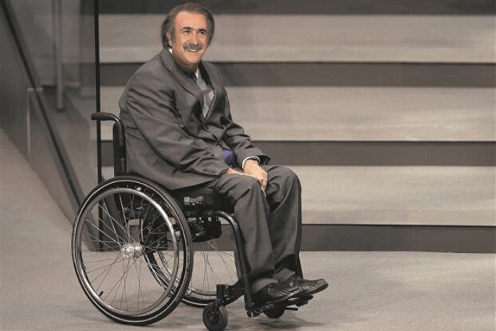 Ο Λάκης Λαζόπουλος καθισμένος σε αναπηρικό αμαξίδιο