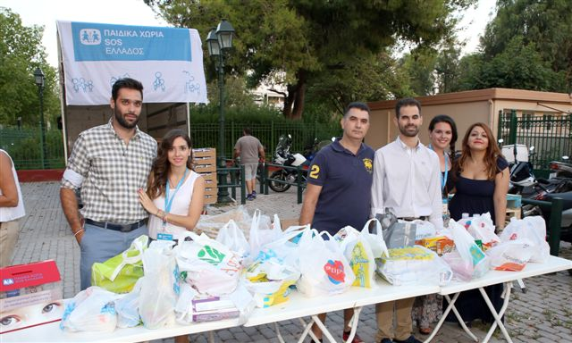 Ο Β. Αυγουλάς στο πάγκο με τα τρόφιμα μαζί με εθελοντές συνεργάτες του