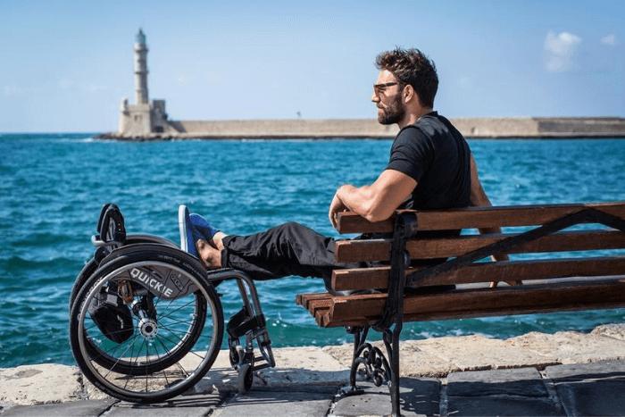 Ο Αντώνης σε παγκάκι με τα πόδια του ακουμπισμένα στο αμαξίδιο
