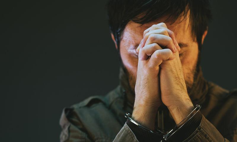 άντρας με χειροπέδες κρύβει το πρόσωπο του
