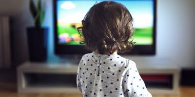 παιδιάκι παρακολουθεί τηλεόραση
