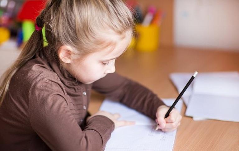 Παιδί γράφει σε τετράδιο