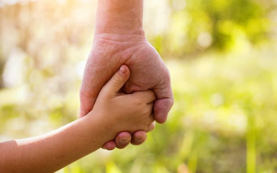 παιδικό χέρι κρατάει χέρι κηδεμόνα