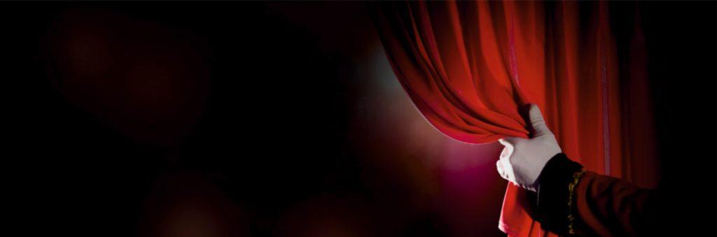 Χέρι που ανοίγει κουρτίνα σε θεατρική παράσταση