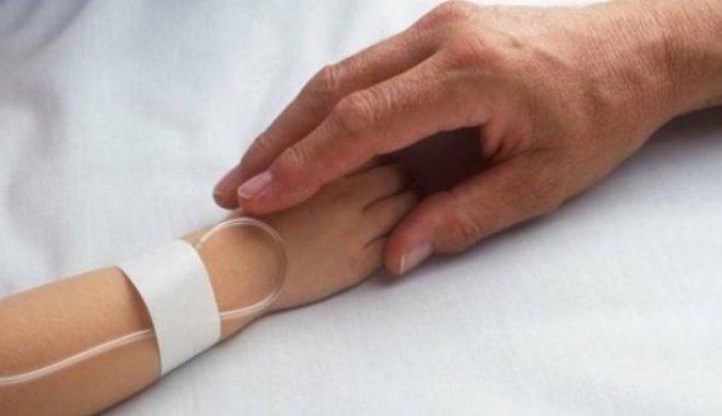 Το χέρι ενός ενήλικα κρατάει το χέρι ενός παιδιού που νοσηλεύεται στο νοσοκομείο