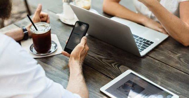 2 άνθρωποι σε τραπέζι με κινητό, τάμπλετ και λάπτοπ