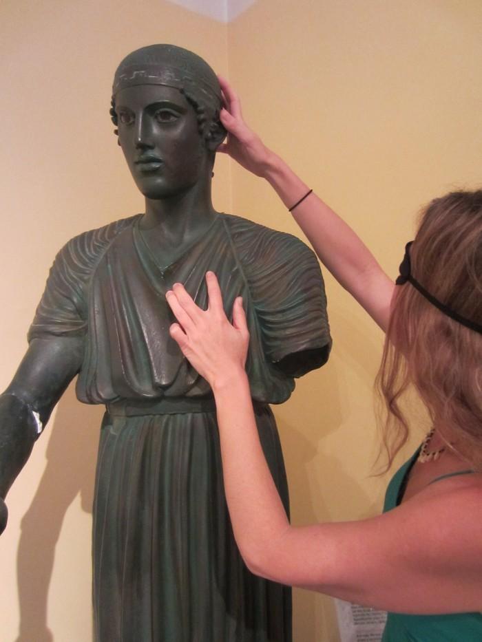Κοπέλα με μάσκα αγγίζει άγαλμα στο μουσείο αφής