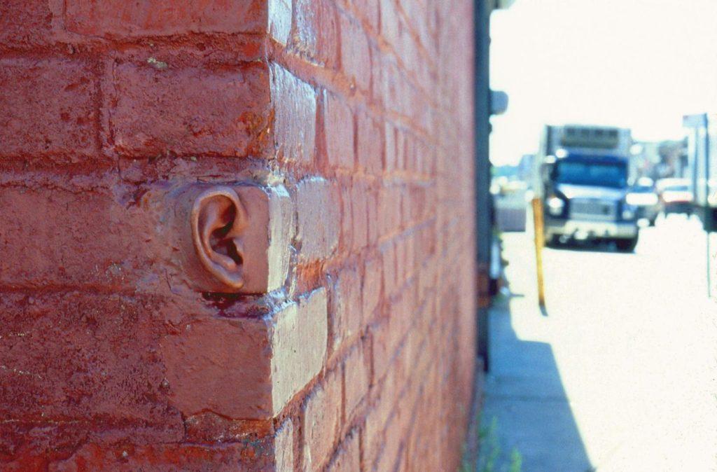 συμβολική φωτογραφία ανθρώπινο αυτί που ξεφυτρώνει από τούβλινο τοίχο