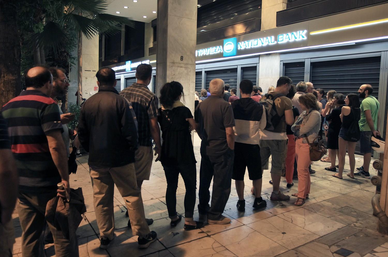 σχηματισμένη ουρά ανθρώπων έξω από τράπεζα