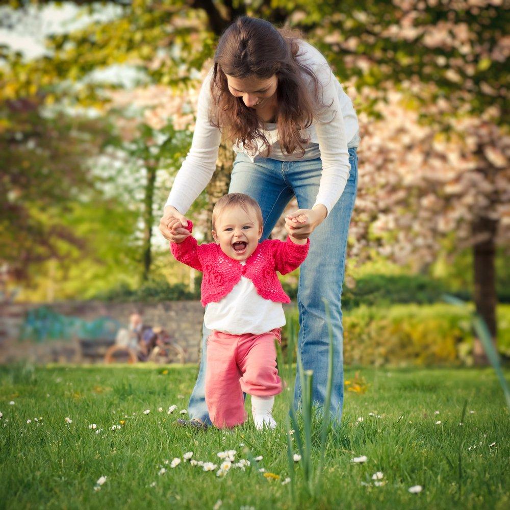 παιδί περπατάει με τη βοήθεια της μαμά του