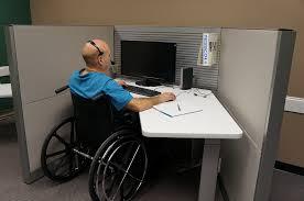 Άτομο με αναπηρία, σε καροτσάκι που εργάζεται σε υπολογιστή.