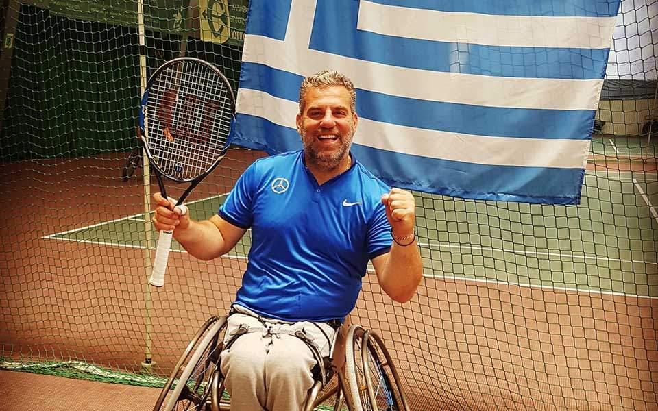 Ο Γιώργος Λαζαρίδης σε αμαξίδιο με την Ελληνική σημαία πίσω του και μια ρακέτα του τέννις.