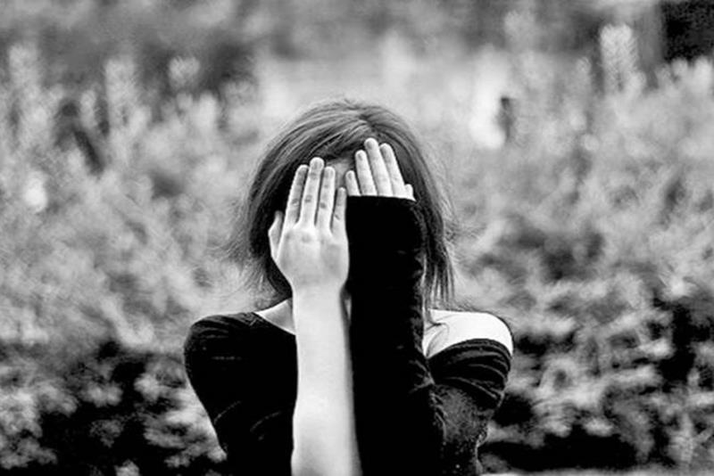 Ένα κορίτσι που κρύβει με τα χέρια της το πρόσωπό της. Το κορίτσι αυτό από τη μια έχει μακρύ μανίκι και από την άλλη κοντό.