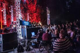 φωτογραφία από την συναυλία του Αλκίνοου Ιωαννίδη, οπου παρίστανται άτομα με αμαξίδια. και μαζί με τον τραγουδιστή επι σκηνής βρίσκεται και μία γυναίκα που λέει τα τραγούδια του στην νοηματική.