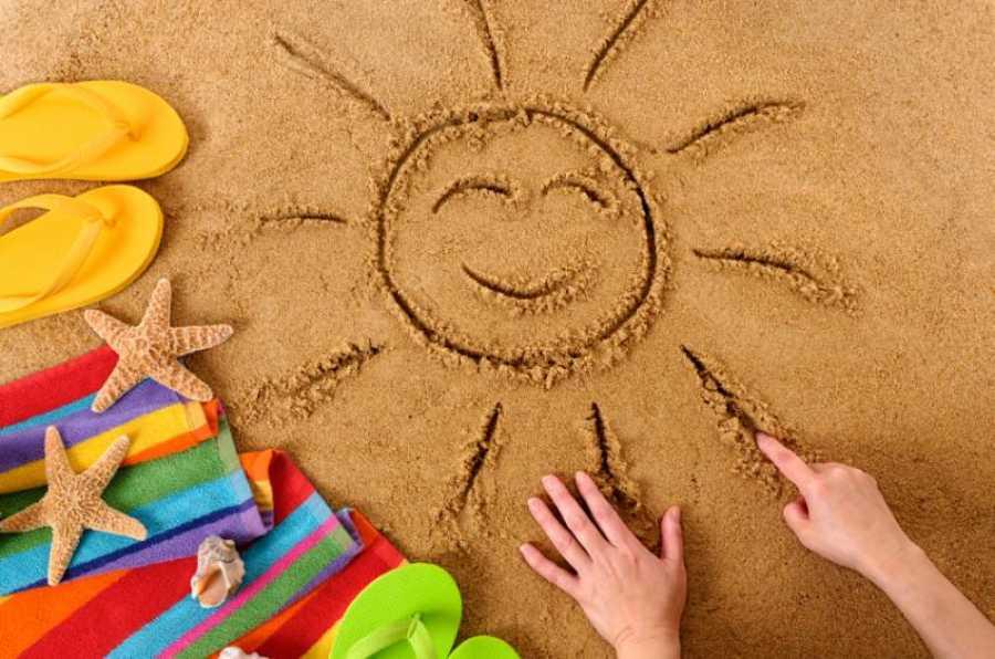 παιδί σχεδιάζει ήλιο στην παραλία με την άμμο