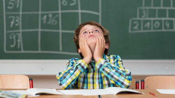 παιδί σε τάξη πίσω ο πίνακας έχει ασκήσεις μαθηματικών