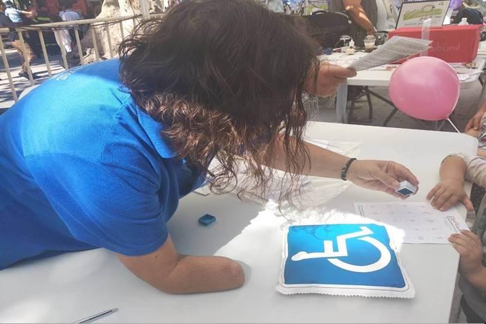 κοπέλα από τον Παγκρήτιο Σύλλογο με ένα χέρι ζωγραφίζει με παιδιά