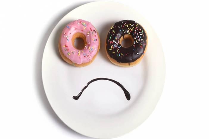 Δύο ντόνατ σε ένα πιάτο σχηματίζουν ένα λυπημένο προσωπάκι