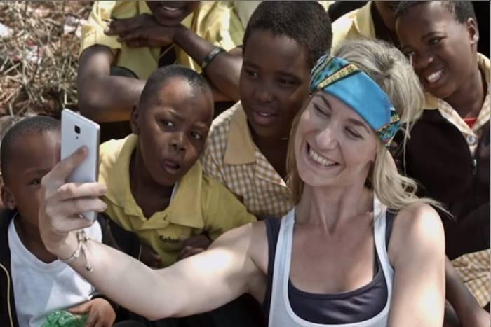 εθελόντρια βγάζει σέλφι με παιδιά