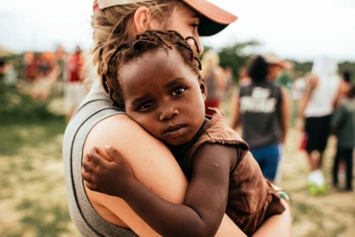 παιδί σε αγκαλιά εθελόντριας