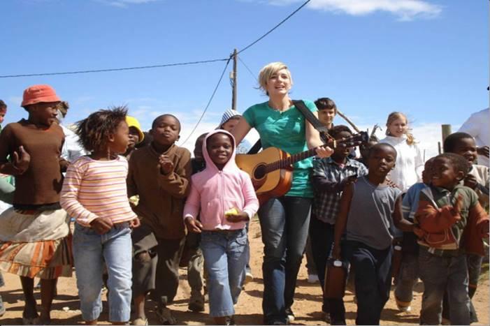 Κοπέλα με κιθάρα και ομάδα παιδιών τραγουδάνε
