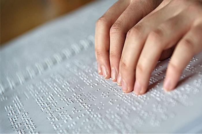 Χέρια σε βιβλίο braille διαβάζουν