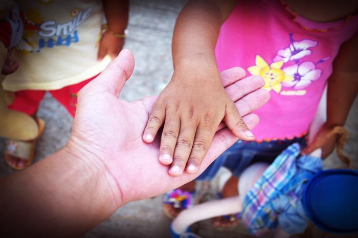 Χέρι που κρατάει χέρι προσφυγόπουλου