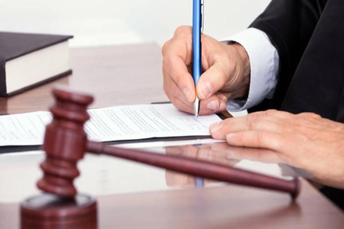 άνδρας υπογράφει χαρτιά
